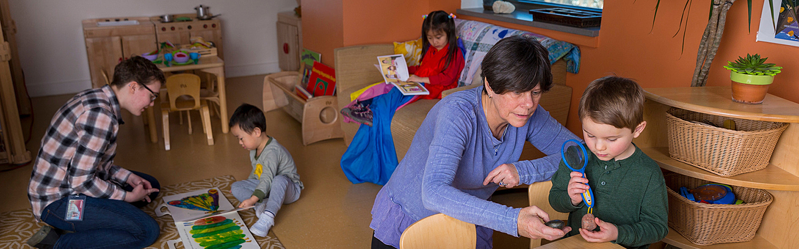 Adult reading with small child on the left. Young child reading in the background. Adult looking at objects with a magnifying glass with another small child on the right.