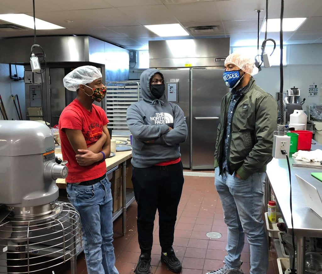 Team members of the nonprofit Mentoring Positives in an industrial kitchen. Mentoring Positives works to build strong, trusting relationships, positive attitudes, and life skills in youth through mentoring and social youth entrepreneurship.